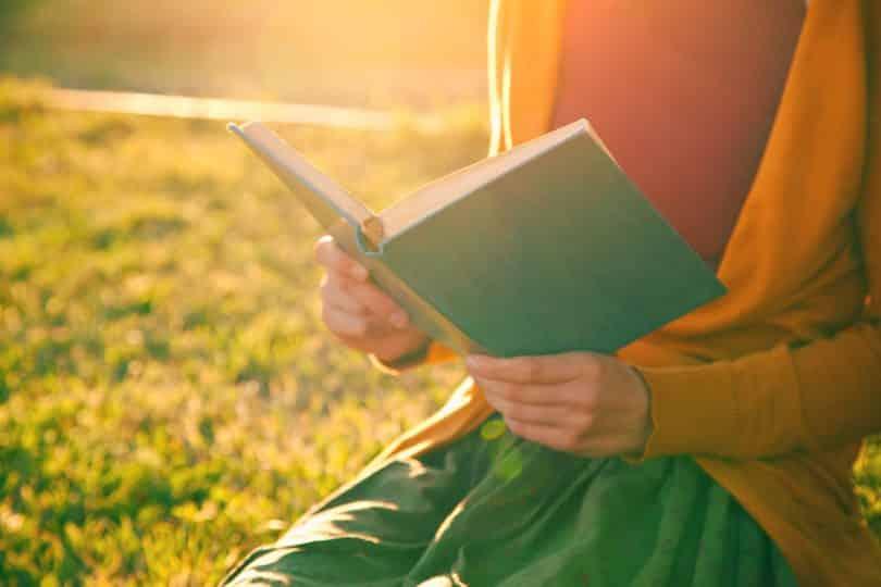 Mãos de mulher segurando livro com sol refletindo