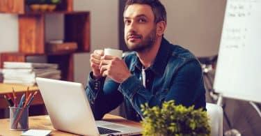 Homem branco de barba castanha, sentado em frente a uma mesa de escritório, enquanto segura uma caneca branca.