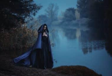 Mulher branca com roupas e capa escuras, ao lado de um lago.