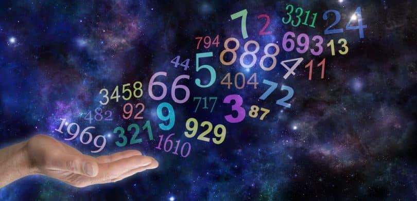 Mão com números flutuando e universo ao fundo