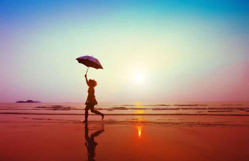 Mulher correndo na areia da praia segurando guarda-chuva.
