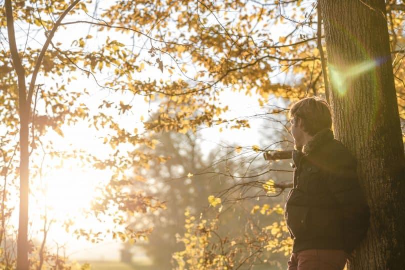 Homem encostado em uma árvore olhando para o lado.
