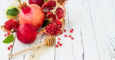 Imagem de frutas como romã, maçã e mel, ingredientes para celebrar o ano novo judaíco.
