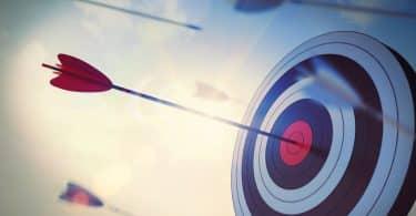 Alvo com flechas acertada no meio e flechas voando
