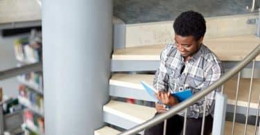 Garoto sentado em escada lendo livro