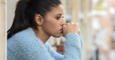 Mulher com expressão triste e cotovelos apoiados com mãos em frente o rosto