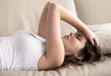 Mulher deitada no sofá com mãos na cabeça e olhos fechados