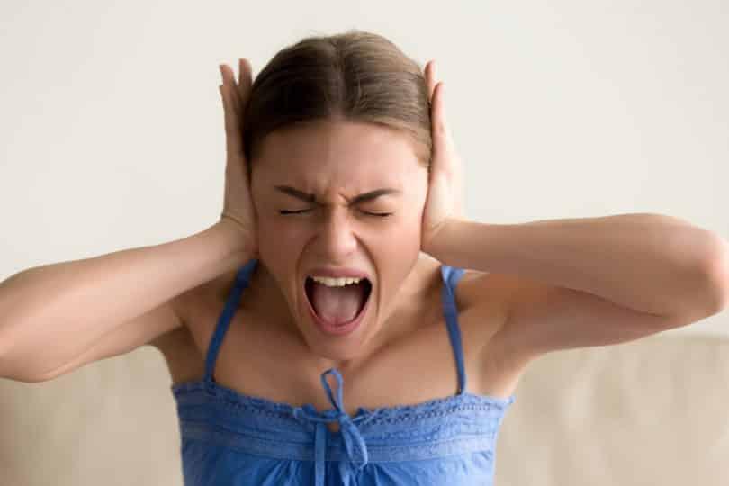 Mulher com mãos nos ouvidos e expressão de grito