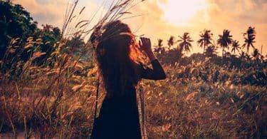 Silhueta de mulher em campo com sol ao fundo