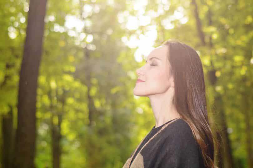 Mulher em pé de perfil com árvores ao fundo