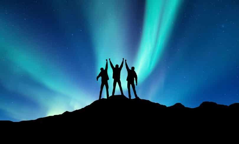 Silhueta de três homens em cima de uma montanha celebrando.