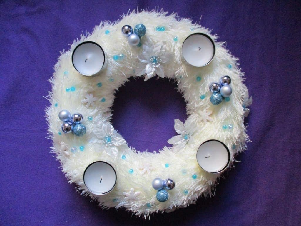 Imagem de uma linda guirlanda de natal na cor branca decorada com velas, flores brancas e azuis e bolinhas azuis e pratas.