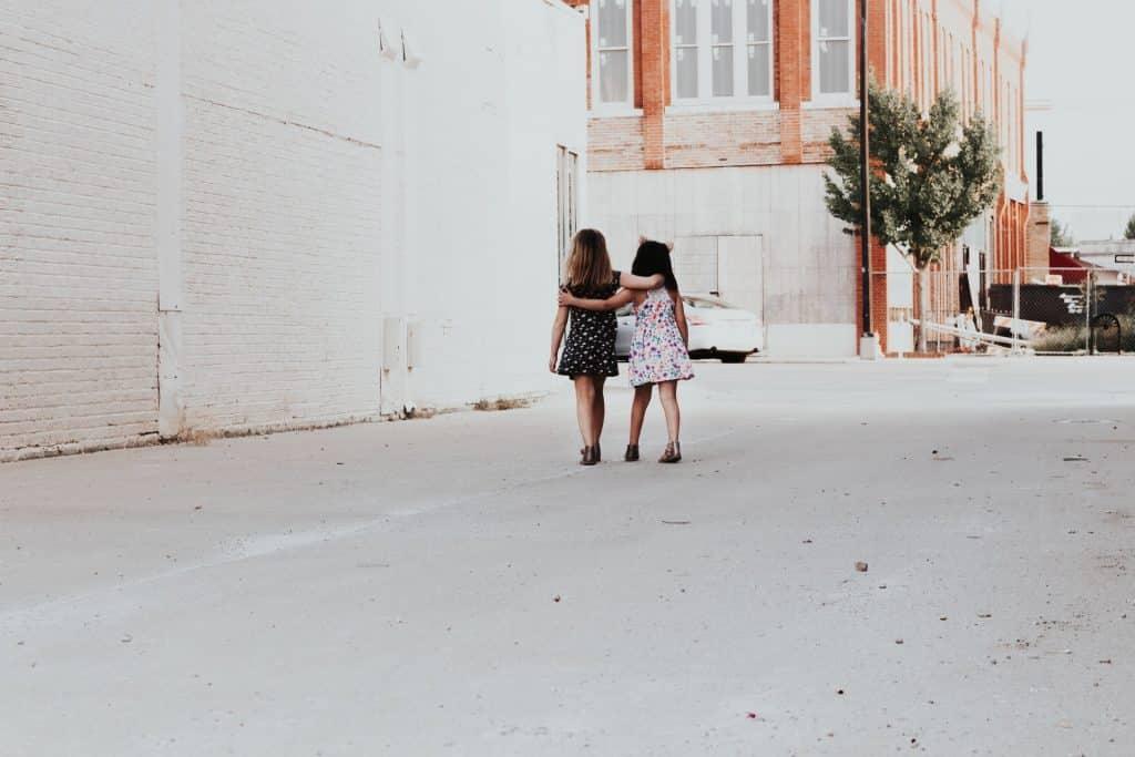 Duas meninas de costas se abraçando.