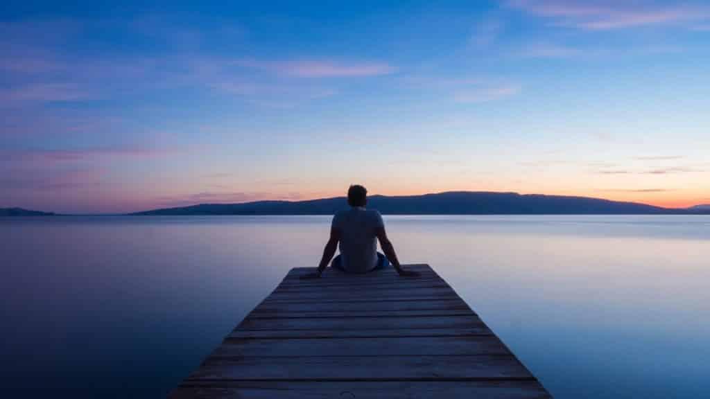 Homem sentado em um píer olhando a paisagem.