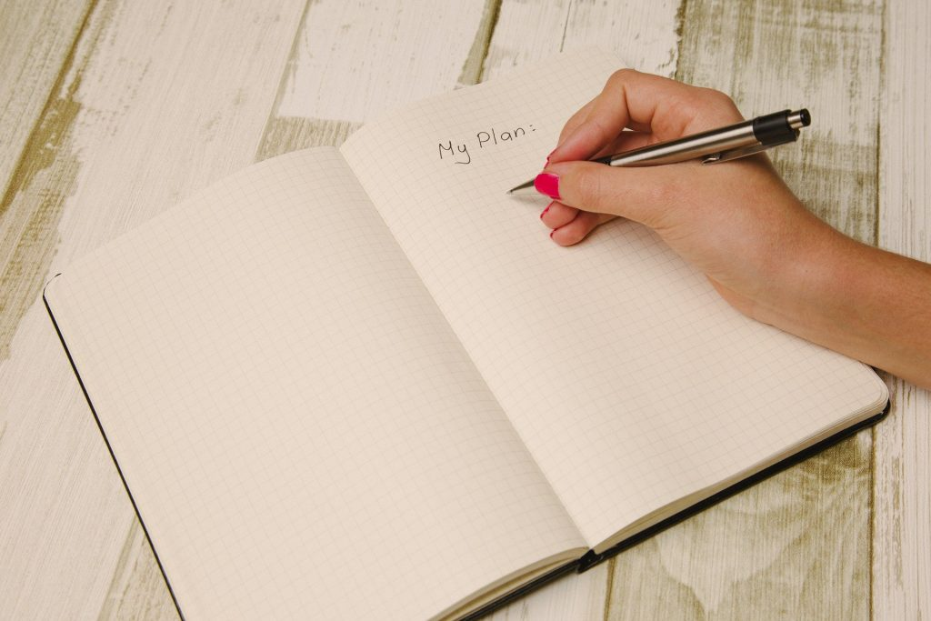 Imagem de um caderno de planejamento sobre uma mesa de madeira clara. Uma mulher segura uma caneta em suas mãos e começa a escrever o seu planejamento para o ano de 2021.