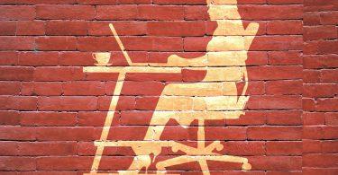 Imagem artística da silhueta de uma mulher empreendedora sentada frente à uma mesa com o seu computador. A imagem está refletida em uma parede feita de tijolos vermelhos.
