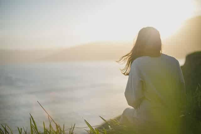 Mulher de costas com cabelos ao vento olhando para o mar e o sol refletindo ao fundo
