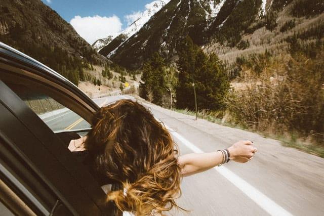 Mulher branca com a cabeça para fora da janela de um carro na estrada.