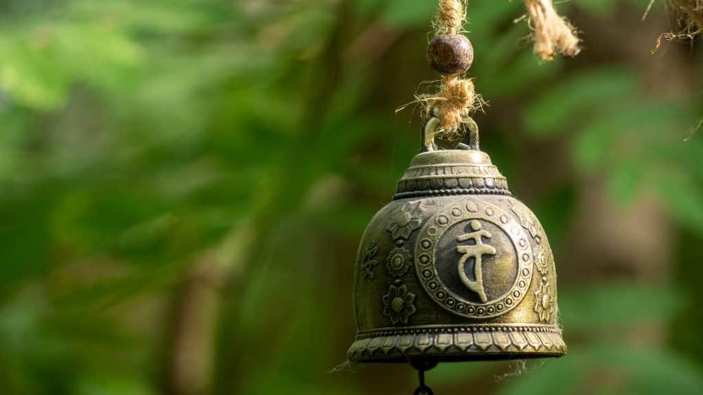 Imagem de um lindo e antigo sino tibetano suspenso por uma corda.