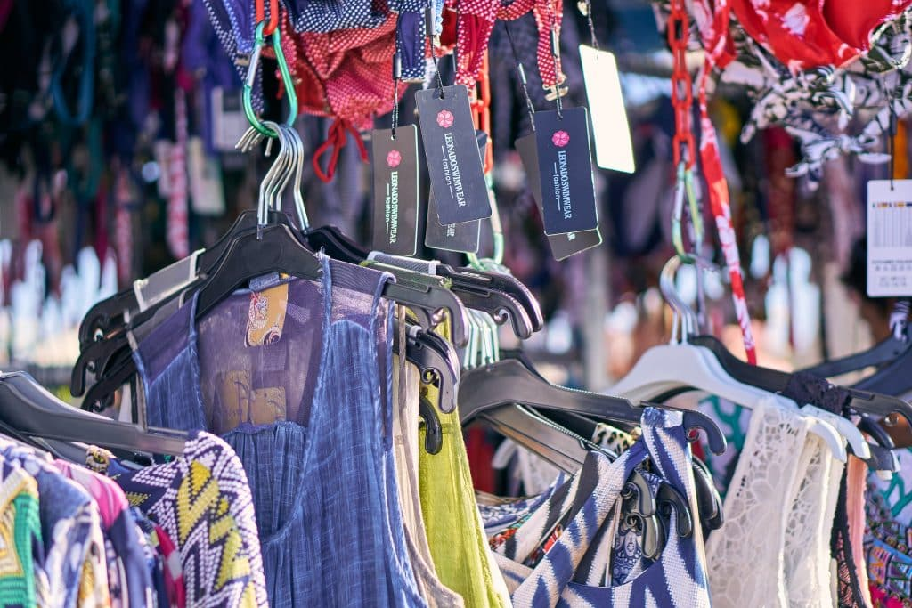 Imagem de uma tenda com uma variedade de roupas femininas para serem comercializadas.