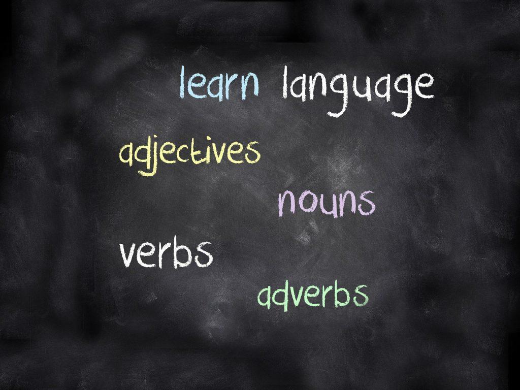 Imagem de um quadro negro com várias palavras escritas em inglês: learn, language, verbs, nouns para serem aprendidas durante uma aula de idiomas.