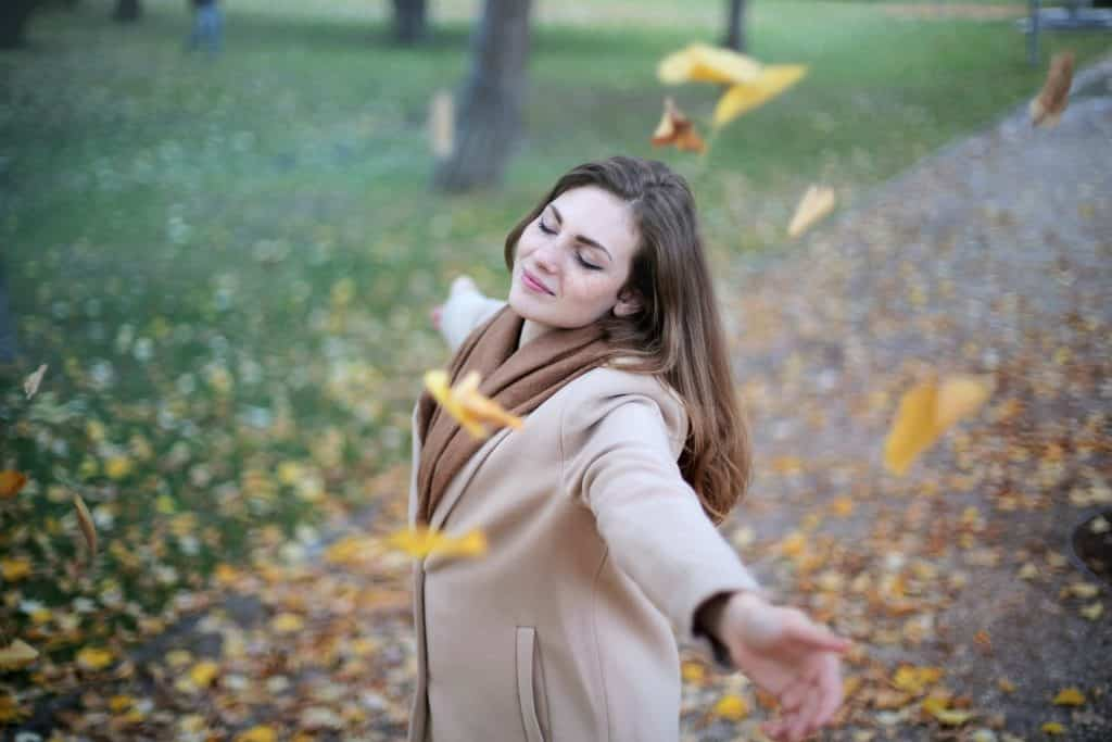 Mulher branca de braços abertos numa praça com folhas caindo em cima dela.