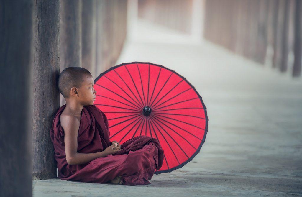 Imagem de um jovem budista sentado e encostado em um tronco de árvore. Ao lado dele um guarda-chuva vermelhor aberto. Ele está meditando.