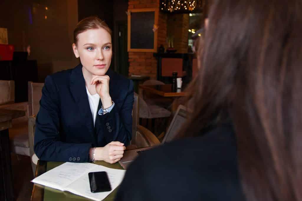 Imagem de duas mulheres empreendedoras fazendo uma reunião de negócios em um restaurante. Elas estão usando camisa social e um terno escuro. Uma delas aparece estar apreensiva.