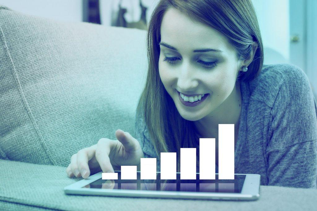 Imagem de uma mulher empreendedora usando o seu tablet para analisar os gráficos de suas finanças.
