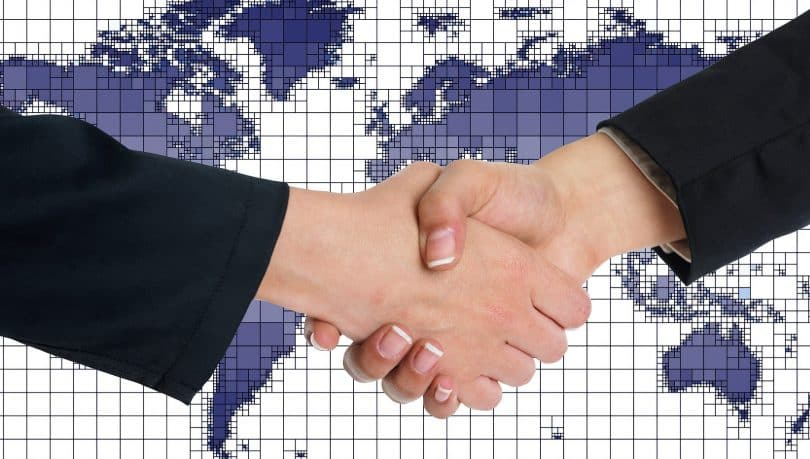 Imagem das mãos de duas mulheres emmpreendedoras se cumprimentando. Ao fundo a imagem de um mapa, nas cores roxo e branco.