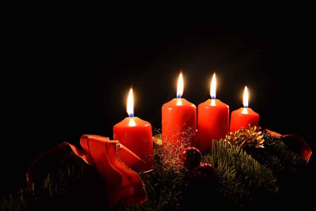 Imagem de um lindo arranjo composto por quatro velas na cor vermelha. Elas estão acesas e dispostas sobre um suporte decorado com ramos de árvores na cor verde, pinhas, bolas vermelhas e laço de fita tamém na cor vermelha,