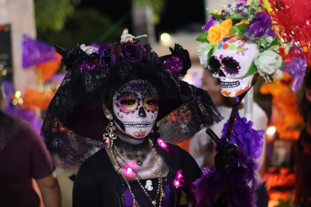 Imagem de uma moça fantasiada de La Catrina, a Deusa da Morte. Ela usa um vestido preto e um chapéu de renda preto. Seu rosto está pintado de caveira. Usa brincos e colares dourados bem grandes.