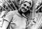 Mulher branca segurando colar no pescoço com expressão sorridente.