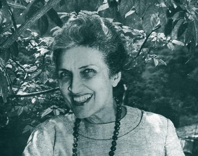 Mulher branca com colar de bolinhas e expressão sorridente.