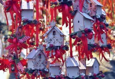 Imagem de várias casinhas de pássaros feita de madeira e pintadas na cor branca e enfeitadas com fitas vermelhas e outros adornos de natal.