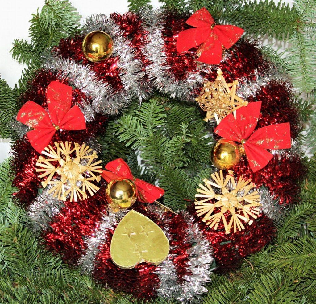 Imagem de uma linda guirlanda de natal feita nas cores verde, vermelha, branca e com enfeites dourados.