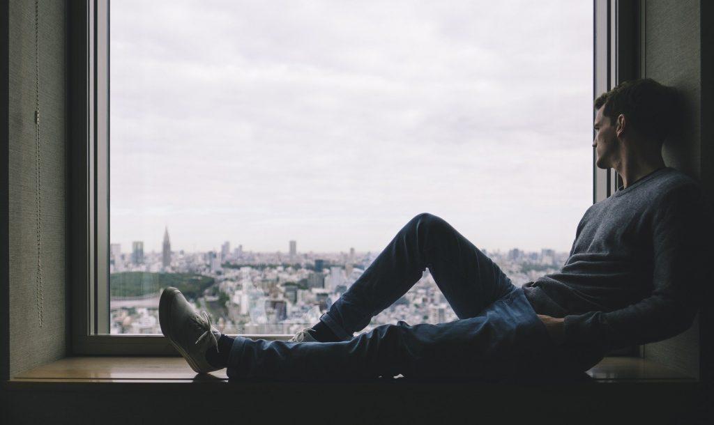 Homem sentado na janela sozinho olhando a cidade ao fundo