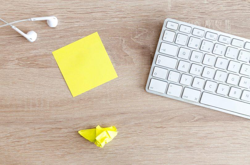 Imagem de um teclado de computador na cor branca. Ao lado um bloco de post-it na cor amarela e um já amassado, junto com um fone de ouvido. Elementos para exercitar a criatividade.