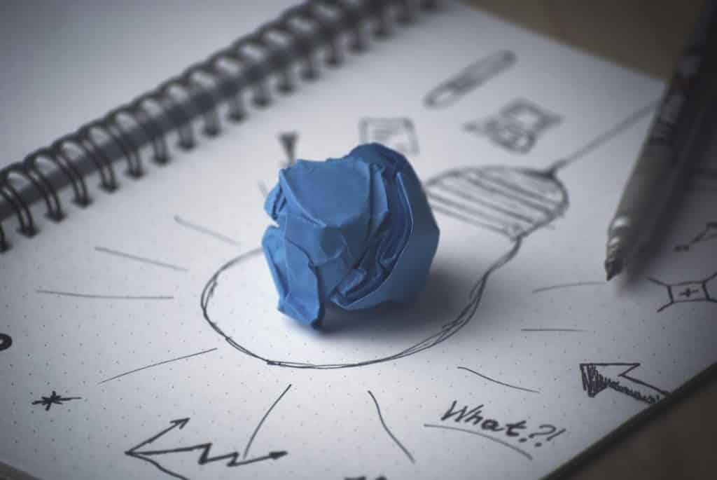 Imagem de um caderno com o desenho de uma lâmpada, setas, gráficos e sobre ele um papel post-it na cor azul, amassado.