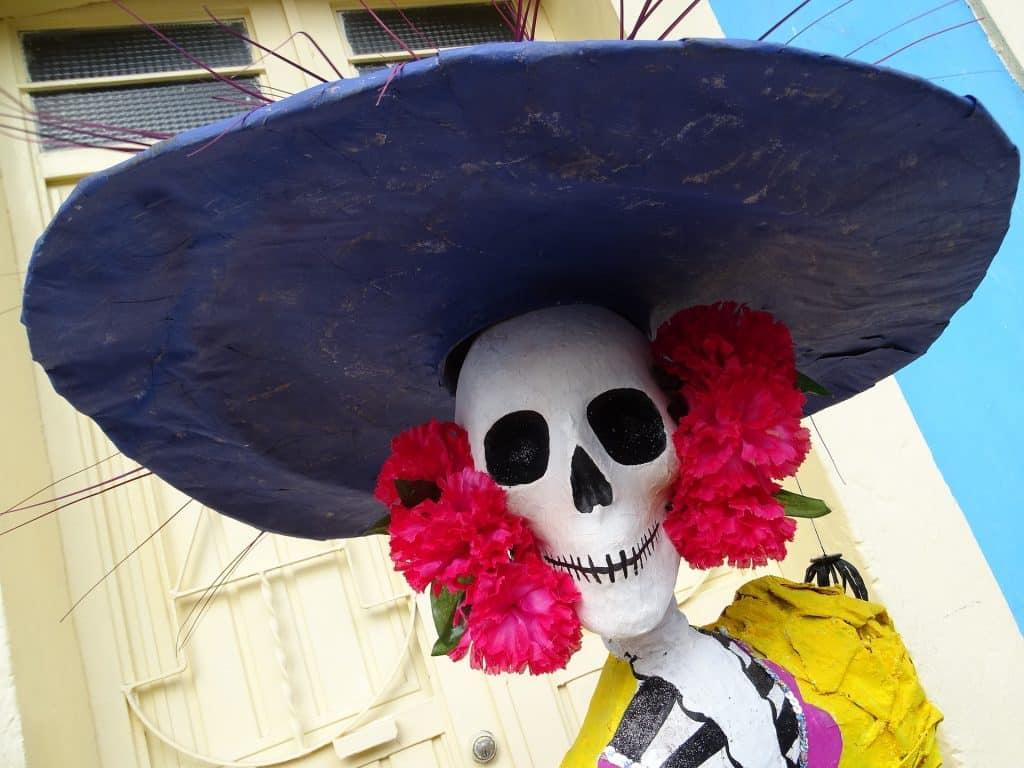 Imagem de uma pessoa fantasiada de La Catrina, a Deusa dos Mortos, festejando o dia dos mortes no México. Ela usa uma máscara de caveira, um chapéu preto e no em torno de suas orelhas um arranjo de flores vermelhas.