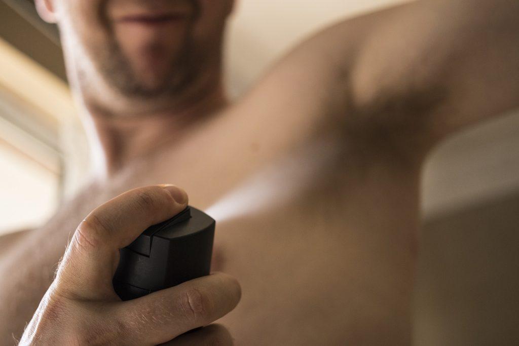 Imagem de um homem sem camisa passando um desodorante aerosol. Ele está se autocuidando.