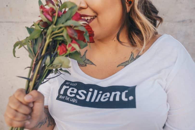 Mulher sorrindo segurando buquê de rosas perto do rosto