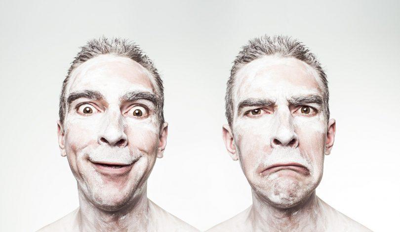 Imagem refletida do rosto de um homem. Em uma delas o homem sorri e em outra ele não consegue sorrir.