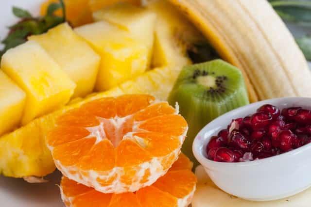 Laranja, abacaxi, kiwi e romã para salada de frutas vista de perto