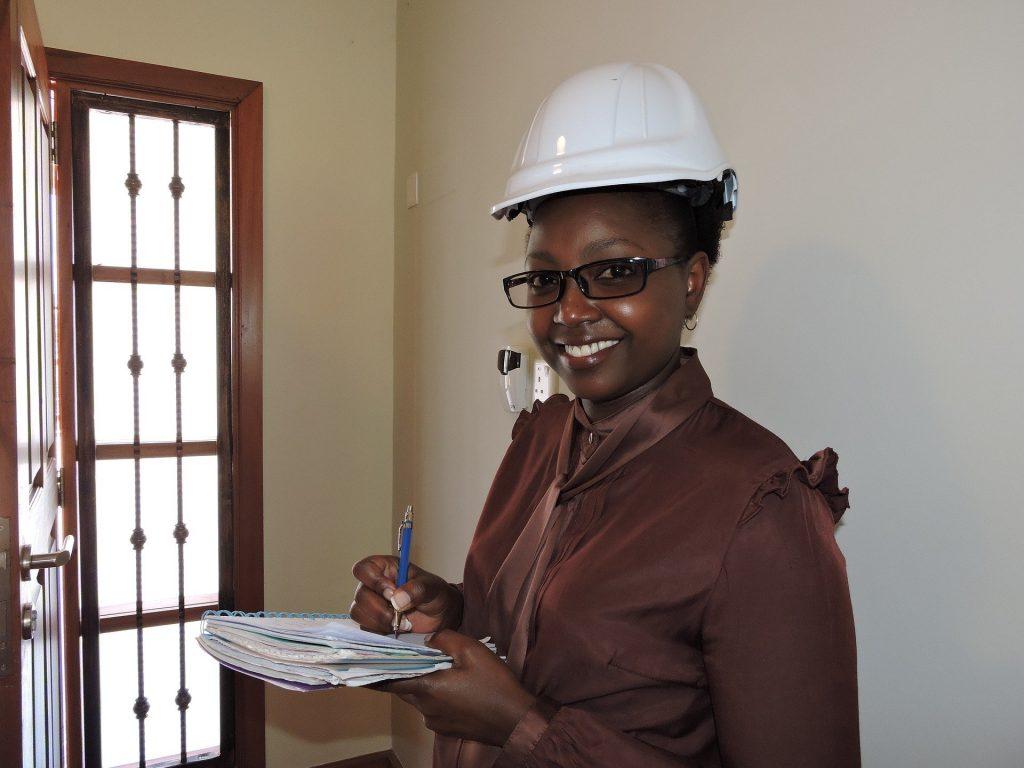 Imagem de uma mulher negra trabalhando. Ela usa um capacete branco, óculos de grau e segura em suas mãos uma caneta e um caderno.