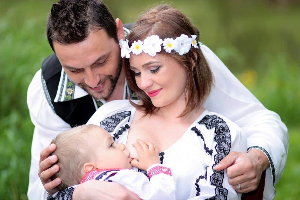 Imagem de um casal. A mulher está amamentando o seu filho. Ela usa um adereço florido na cabeça e ambos vestem uma camisa branca bordada com renda preta.