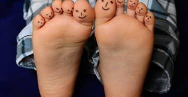Imagem dos pés de uma criança e os dez dedos estão pintados com uma carinha feliz.