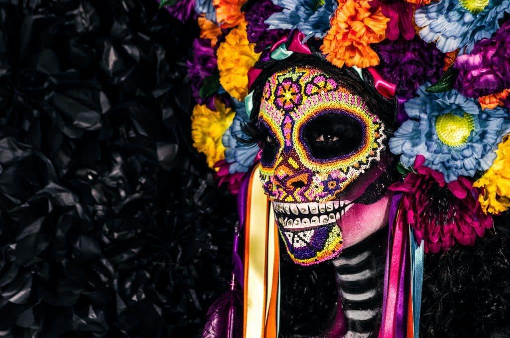 Pessoa com o rosto pintado de caveira com flores