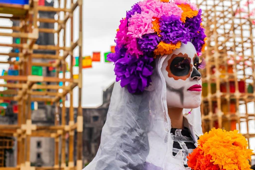 Mulher com rosto pintado de caveira e flores na cabeça