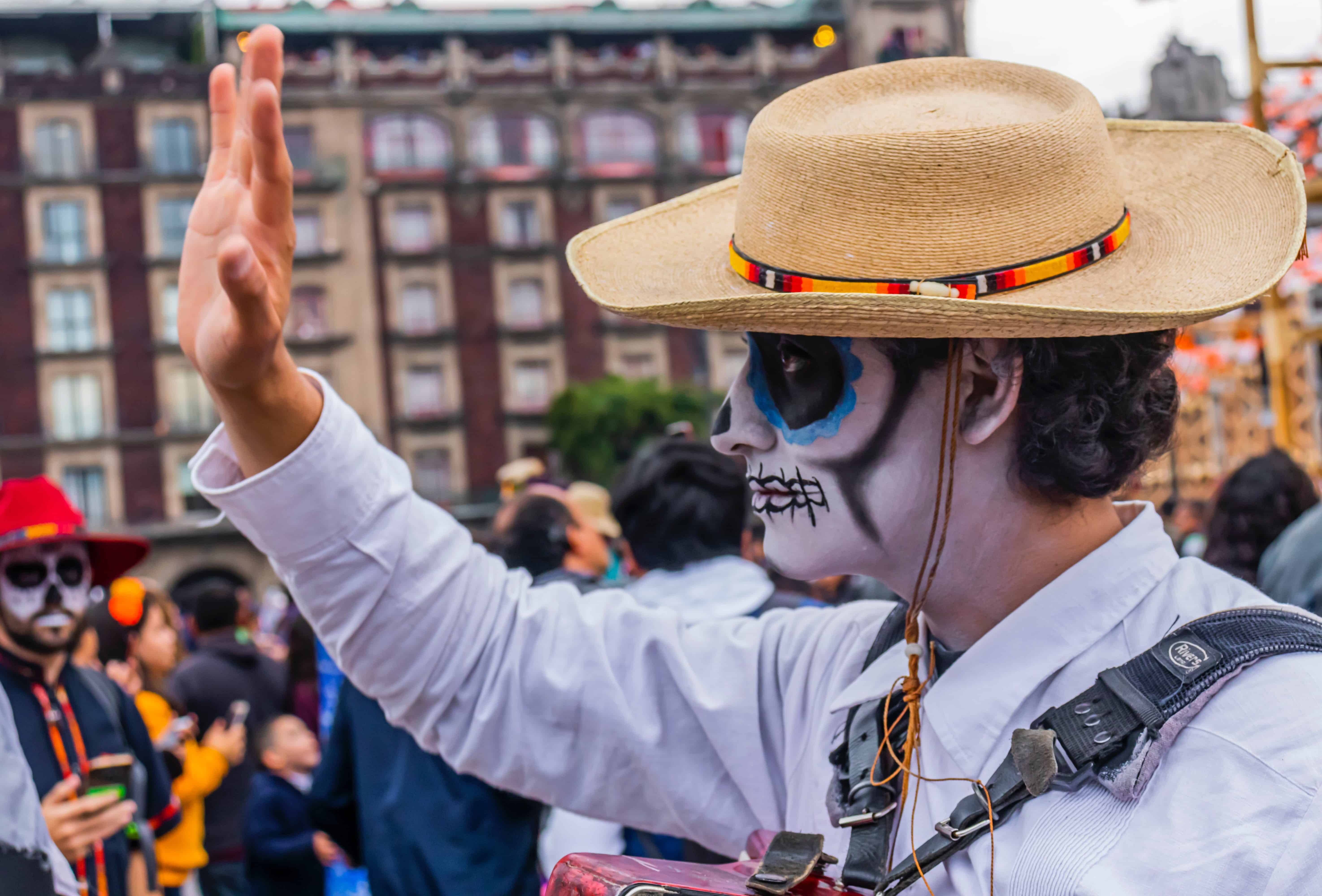 Homem com rosto pintado de caveira usando chapéu e acenando